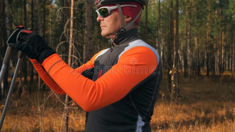 Training an athlete on the roller skaters. Biathlon ride on the roller skis with ski poles, in the helmet. Autumn. Workout. Roller sport. Adult man riding on royalty free stock photography