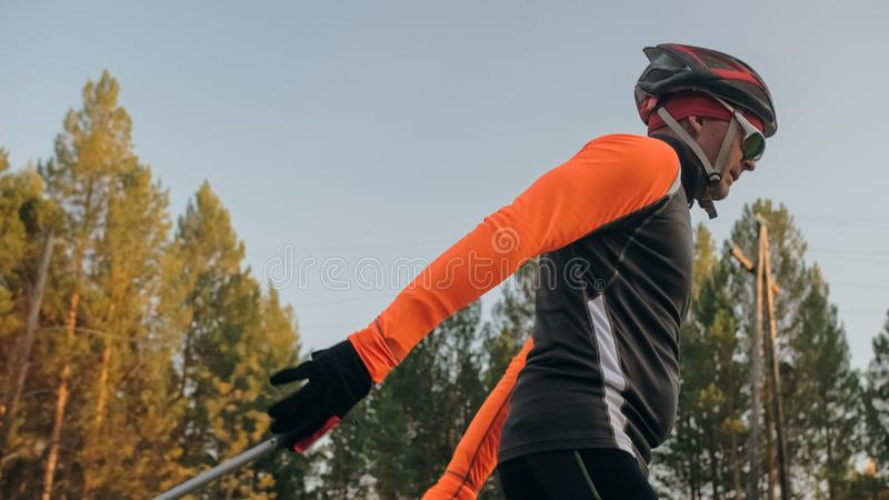 Training an athlete on the roller skaters. Biathlon ride on the roller skis with ski poles, in the helmet. Autumn. Workout. Roller sport. Adult man riding on royalty free stock photos