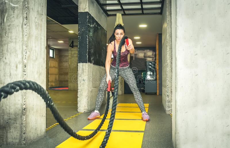 Training of beautiful young and attractive girl making fun and funny faces while she workout on the battle ropes in the gym stock photography
