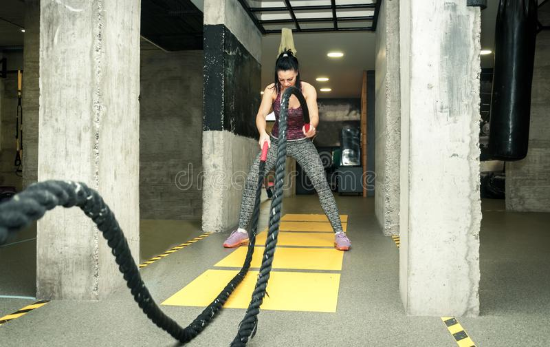 Training of beautiful young and attractive girl making serious face expression while she workout on the battle ropes in the gym stock photography