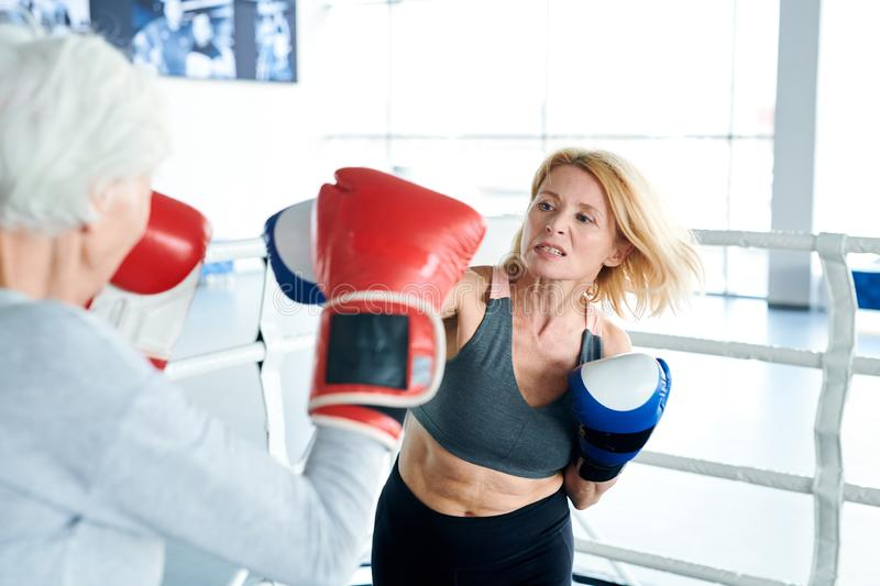 Training on boxing ring. Blonde aggressive women in activewear and boxing gloves hitting her older rival during training on the ring royalty free stock images