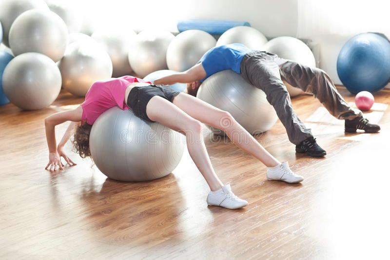Training - couple on pilates balls. A young couple exercising and working out in a room full of pilates balls royalty free stock photos