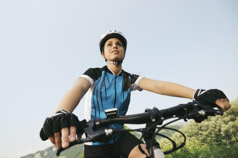 Training der jungen Frau auf Mountainbike und Radfahren in Park lizenzfreies stockbild