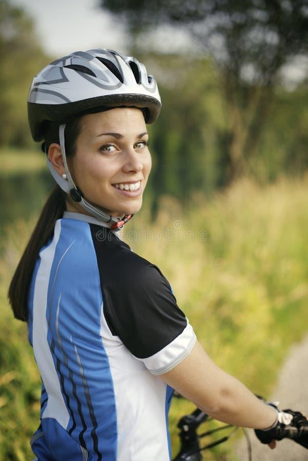 Training der jungen Frau auf Mountainbike und Radfahren in Park stockfotografie