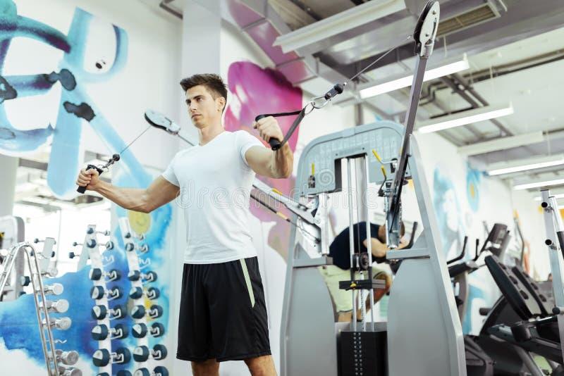 Training des gutaussehenden Mannes in der sauberen modernen Turnhalle stockfoto