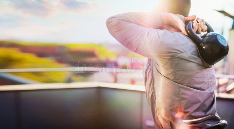 Training des jungen Mannes mit Gewichten auf der Terrasse mit schöner Stadtlandschaft lizenzfreie stockfotografie