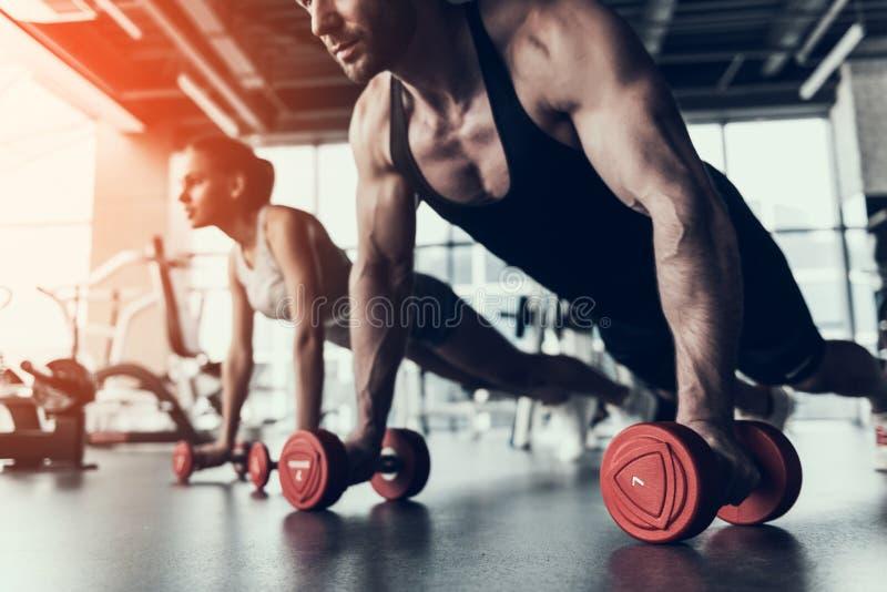 Training des jungen Mannes und der Frau im Fitness-Club stockfotos