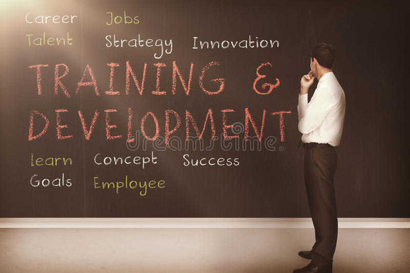 Training and development terms written on a blackboard 3d. Businessman looking at training and development terms written on a blackboard 3d stock illustration