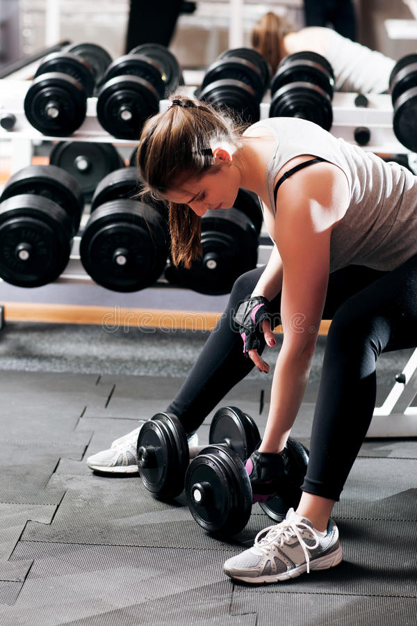 Training with dumbbells young woman, close-up. Attractive female athlete workout with dumbbell at gym. Bodybuilding, armwrestling, fitness concept stock images
