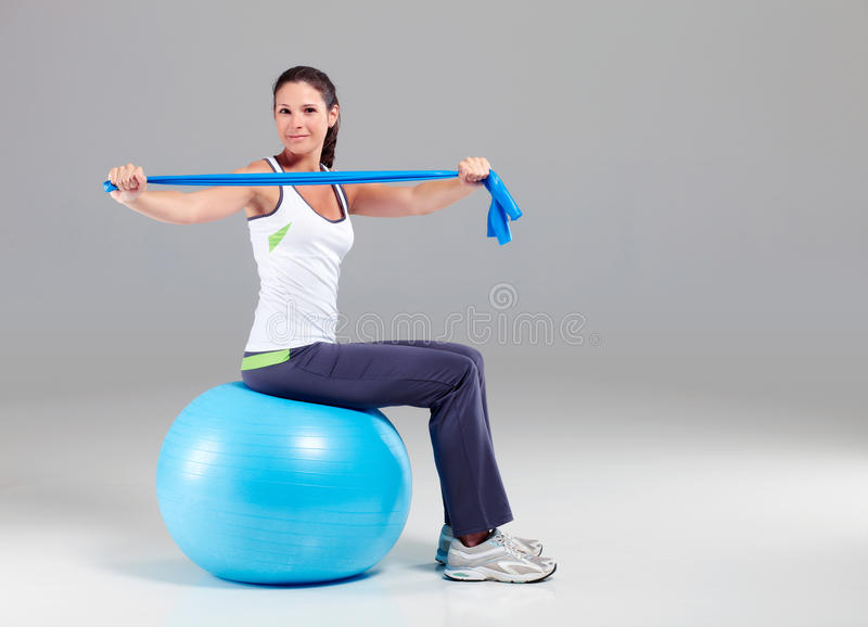Training with elastic band. Young woman exercise with terra band royalty free stock photo