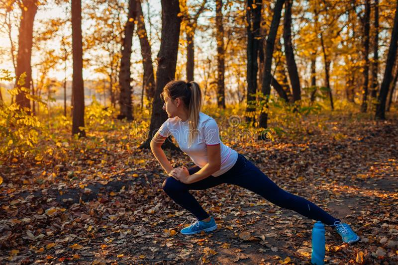 Training and exercising in autumn park. Woman stretching legs outdoors. Active healthy lifestyle royalty free stock photography