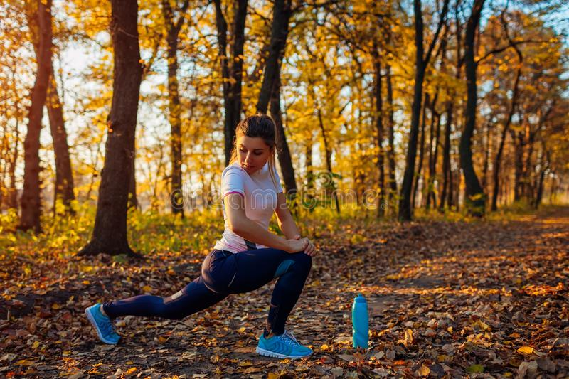 Training and exercising in autumn park. Young woman stretching legs outdoors. Active healthy lifestyle royalty free stock photo