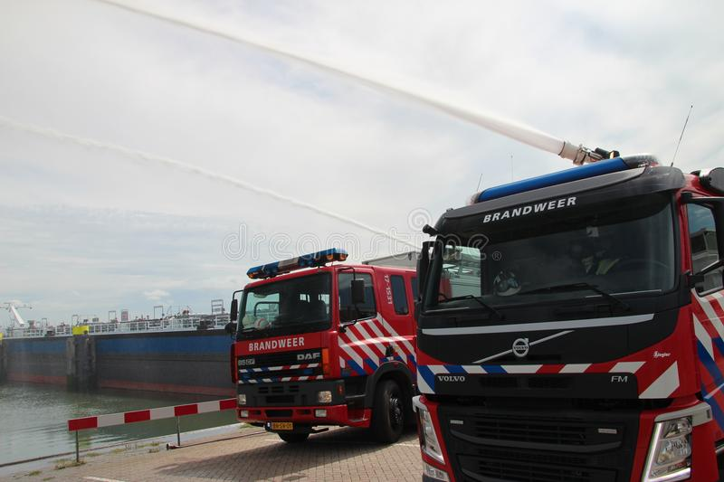 Training with extinguish water jets by the fire brigade in harbor 6100 in the port of Rotterdam in the Netherlands. Training with extinguish water jets by the royalty free stock images