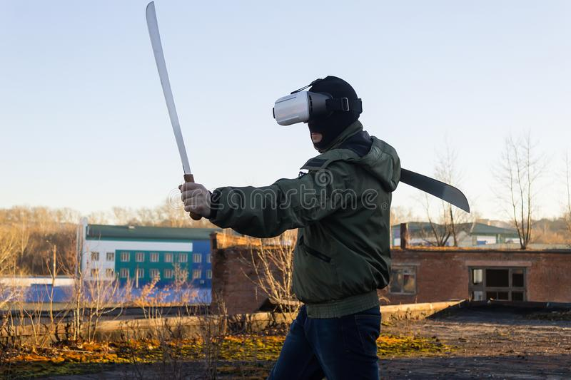 Training a person wearing virtual reality glasses. Training a fighter with swords in virtual reality glasses on the street royalty free stock photo