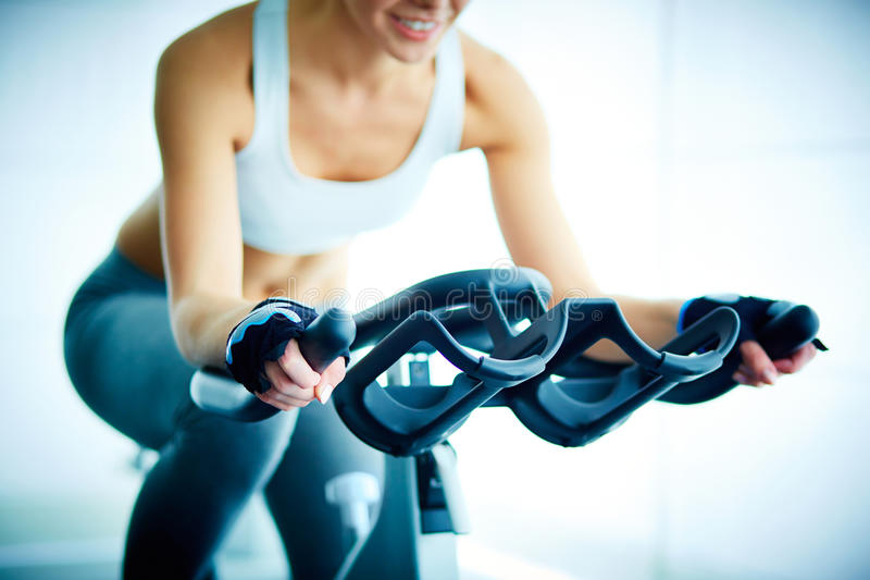 Training in gym. Close-up of young female training on simulator in gym stock photos