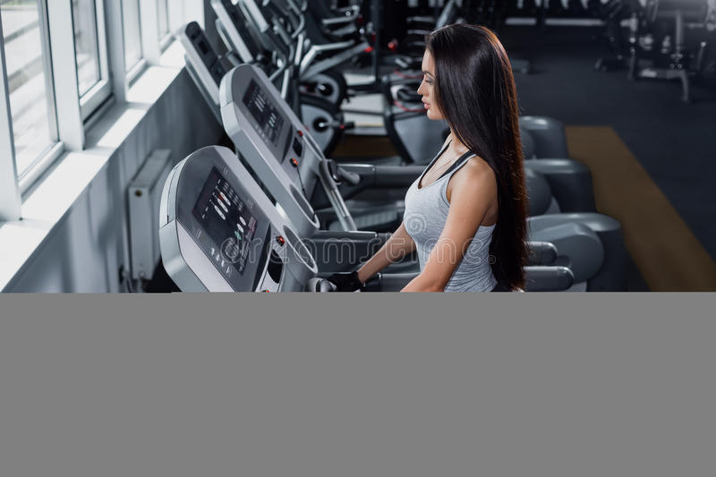 Training in the gym. Fitness girl burn calories on the treadmill royalty free stock photo