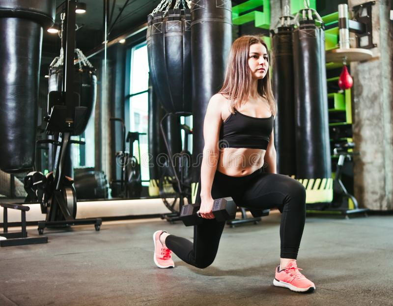 Training legs at the gym. Attractive fit woman doing lunges with dumbbells stock photo