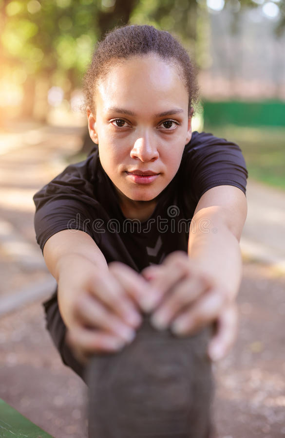 Training outdoors. Fit young woman stretching her legs. royalty free stock images