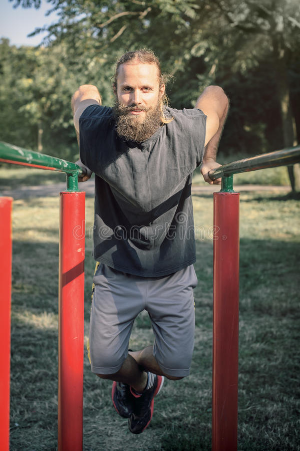 Training outdoors. Man doing biceps and triceps dips training. royalty free stock photography
