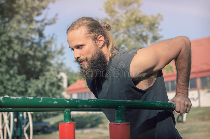 Training outdoors. Man doing biceps and triceps dips training. stock photos