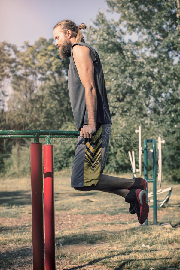 Training outdoors. Man doing biceps and triceps dips training. royalty free stock image