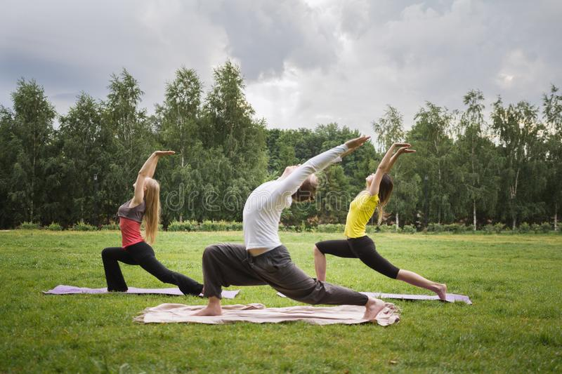 Training in park - instructor shows flexibility exercise for group of girls in park. Early morning royalty free stock image