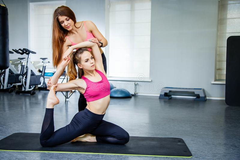 Training with a personal trainer. Trainer helping young woman doing stretching exercise stock photography
