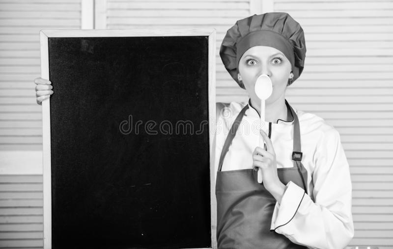 A training school for cooks. Pretty woman holding spoon at empty blackboard. Culinary education in cooking school. Master cook giving at cooking class. Chief stock photos
