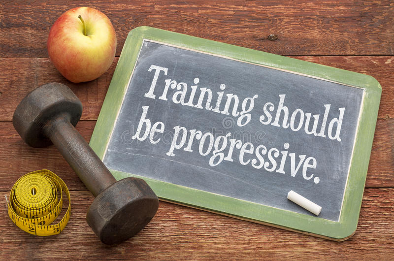 Training should be progressive. Slate blackboard sign against weathered red painted barn wood with a dumbbell, apple and tape measure stock images