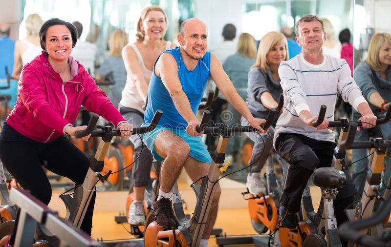 Training in sport club on fitness cycle stock photography