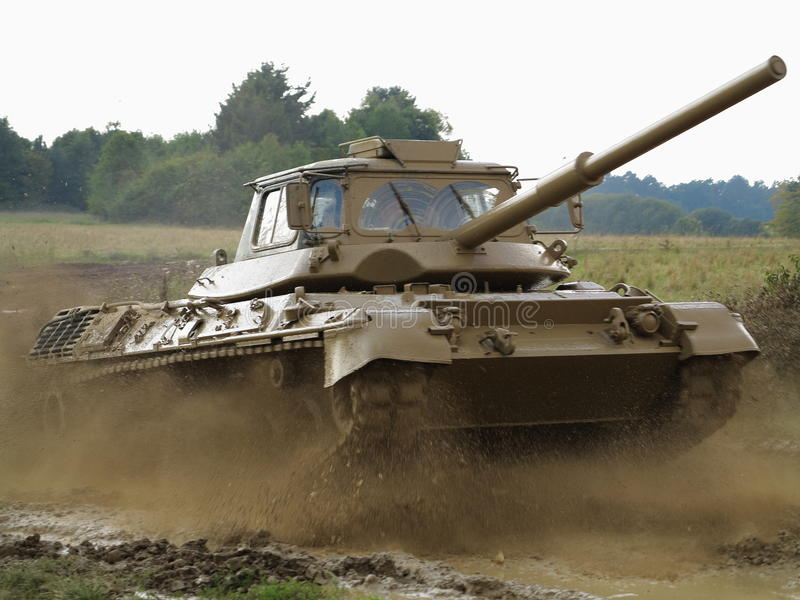 Training tank in action. A german training tank in action - speeding in the muddy field royalty free stock image