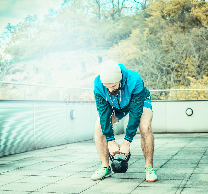 Training on the terrace of the house, overlooking the forest, young man with a beard lifts weights royalty free stock image