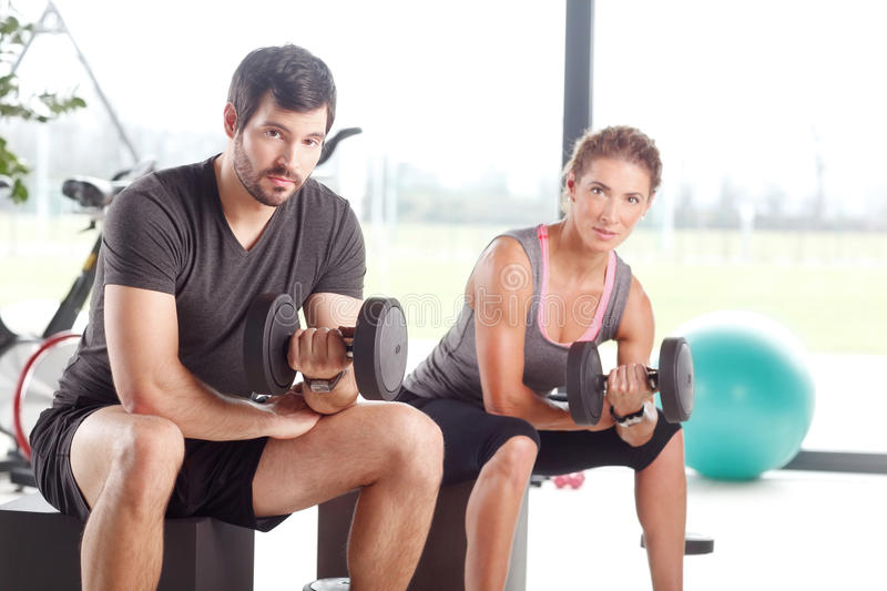 Training together at fitness class. Close-up portrait of women and men lifting barbells during a gym workout at fitness center royalty free stock photography