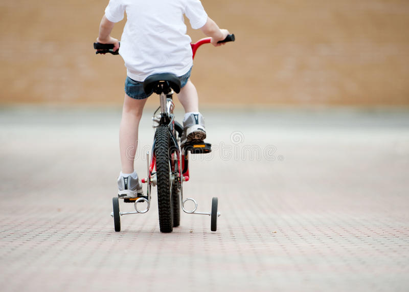 Training wheels. Young child riding a bike with training wheels. Boy is pedaling his red and black bicycle down a brick driveway, wearing shorts and a white tee royalty free stock photography
