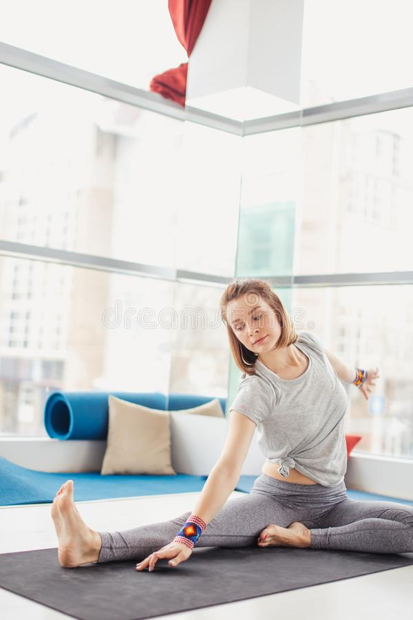 Woman performing yoga pose on mat, healthy lifestyle and fitness concept. Training woman in yoga class making asana exercises doing Head to Knee Forward Bend stock photo