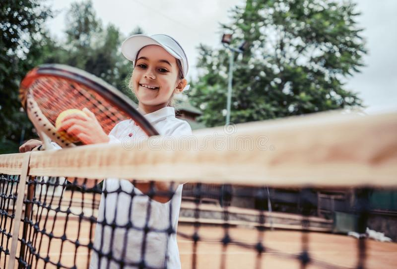 Training for young kid in tennis club. Portrait of little girl athlete looking in the camera near tennis net. Smiling sporty. Tennis player on court. Summer stock images