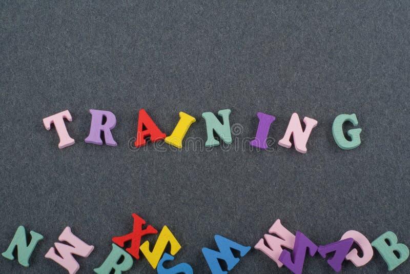 TRAININGS-Wort auf dem schwarzen Bretthintergrund verfasst von den hölzernen Buchstaben des bunten ABC-Alphabetblockes, Kopienrau lizenzfreie stockfotografie