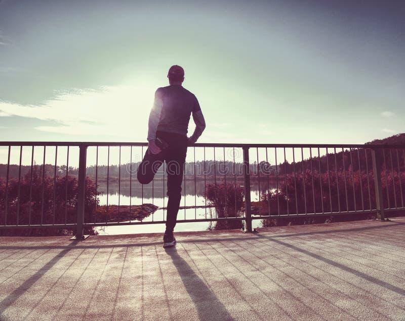 Trainingsläufer Mann tun das Ausdehnen und machen eine Pause von Laufaußenseite lizenzfreies stockbild