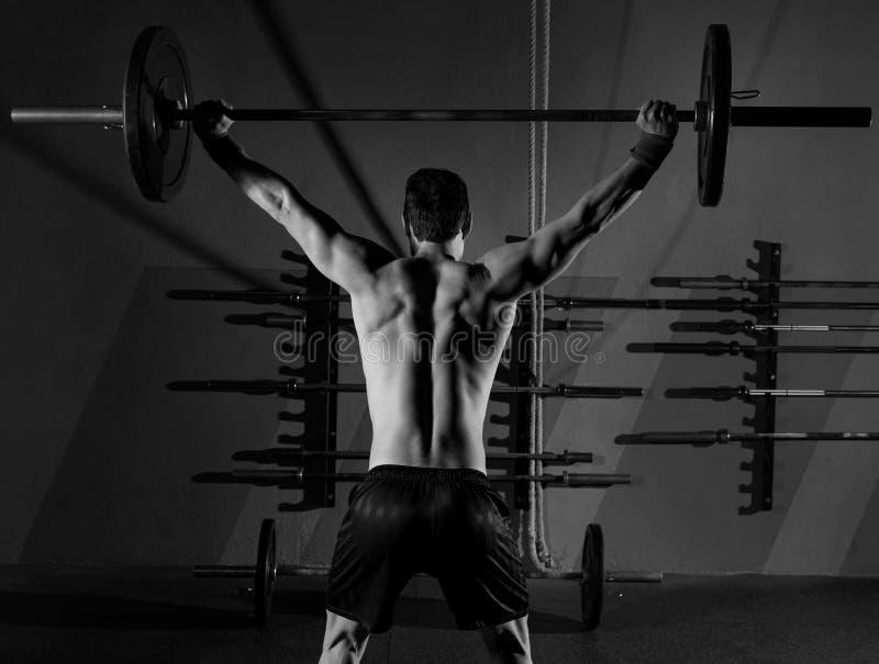 Trainingsturnhalle der hinteren Ansicht des Barbellgewichthebenmannes lizenzfreie stockbilder