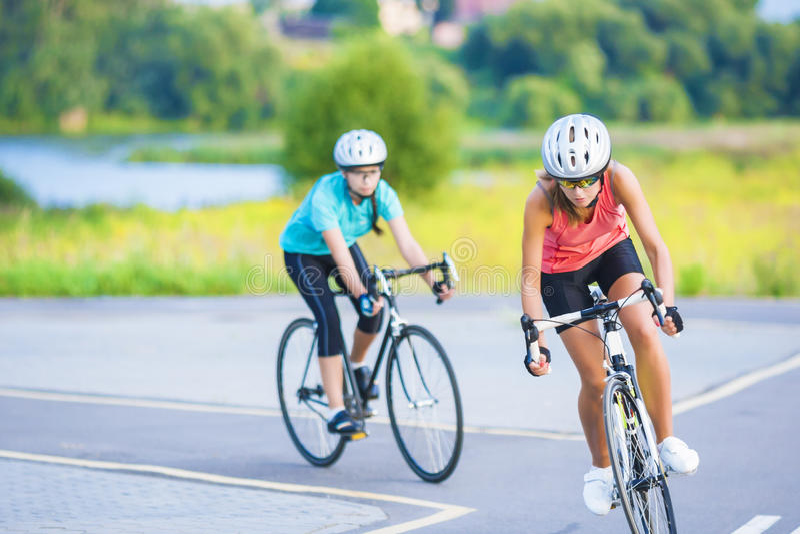 Trainingszyklus der zwei weiblichen kaukasischen Sportlerinnen, die s reiten lizenzfreie stockbilder