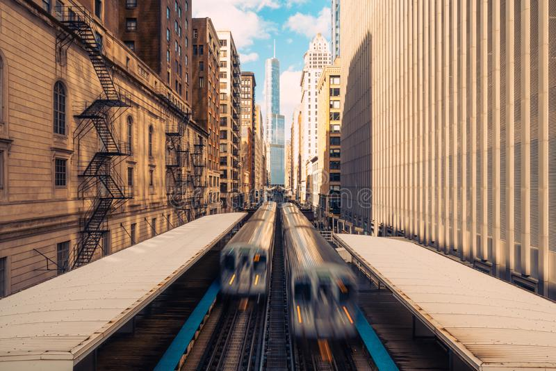 Trains arriving railway station between buildings in downtown Chicago, Illinois. Public transportation, or American city life royalty free stock image