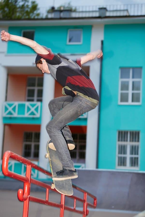 Trains de garçon sur la planche à roulettes dans le skatepark de soirée image stock