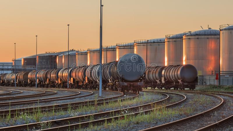 Trains with silos of a petrochemical plant on the background lit by warm light, Port of Antwerp, belgium. Trains with silos of a petrocemical production plant on royalty free stock photos