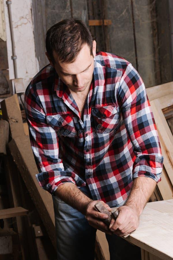 traitement de bois Jeune charpentier masculin sûr travaillant avec du bois images stock