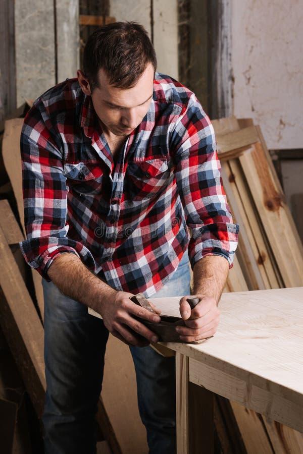 traitement de bois Jeune charpentier masculin sûr travaillant avec du bois image stock