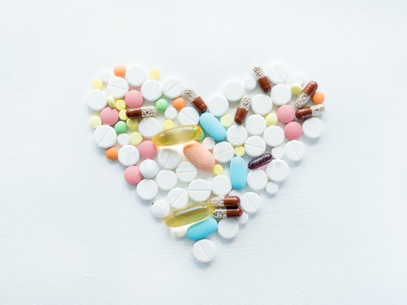 Traitement de maladie de médicament de forme de coeur de mélange de pilule blanc image stock
