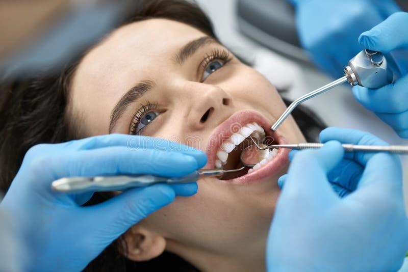 Traitement des dents de la jolie femme dans la clinique dentaire photos stock