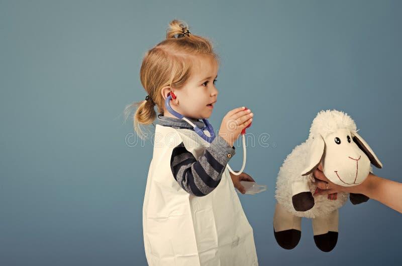 Traitement des enfants Vétérinaire de jeu de garçon avec des moutons de jouet dans la main de mères image libre de droits