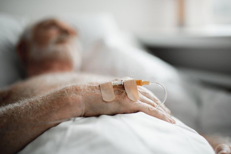 Traitement intraveineux de réception patient tout en se situant dans le lit d'hôpital photo libre de droits