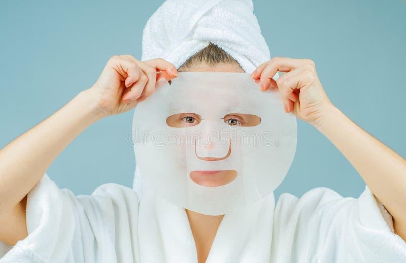 Traitements faciaux de soin et de beauté Belle femme avec une feuille hydratant le masque sur son visage photos libres de droits